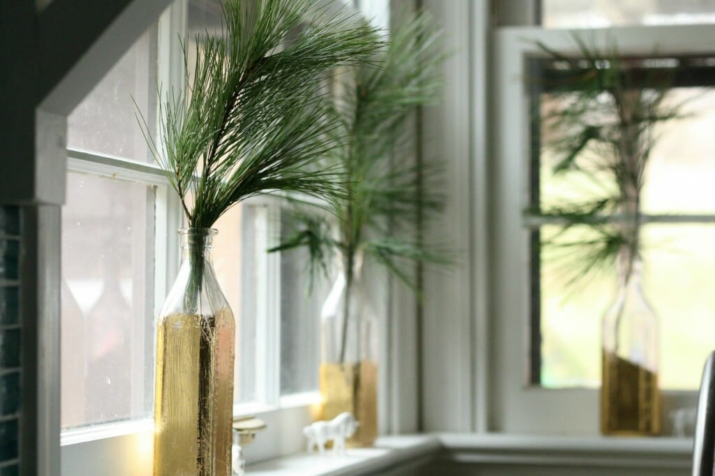kitchen window with gold leafed bottles and evergreen