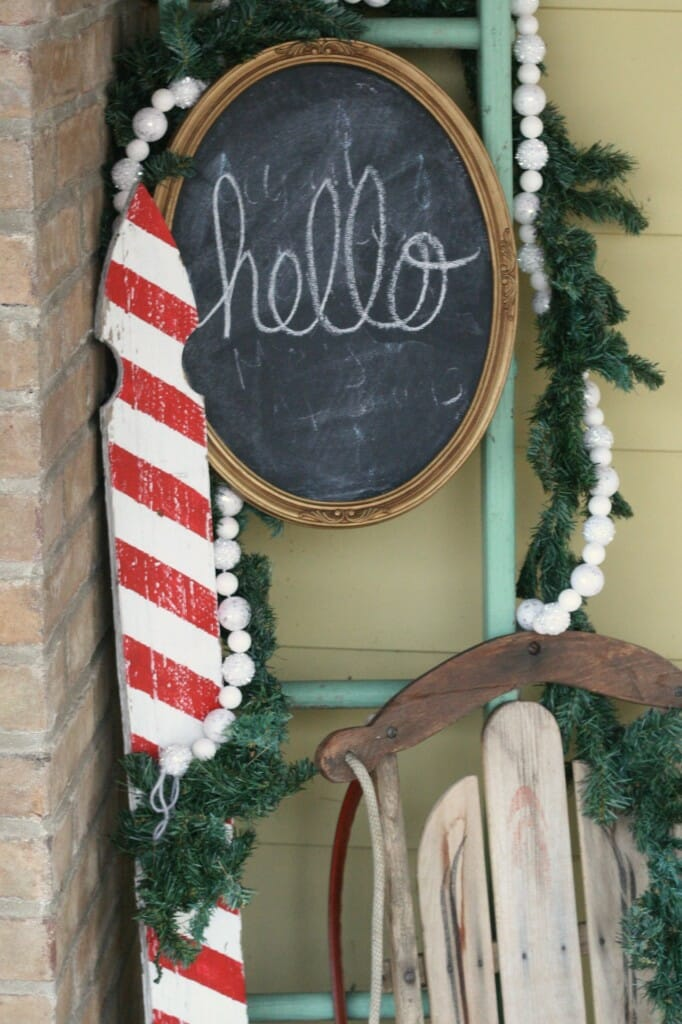 Christmas porch entry with candy cane picket, ladder, garlands, chalkboard