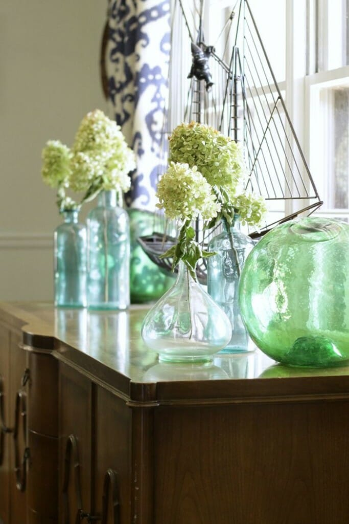 Dining Room Sideboard with green and blue glass and dried hydrangeas