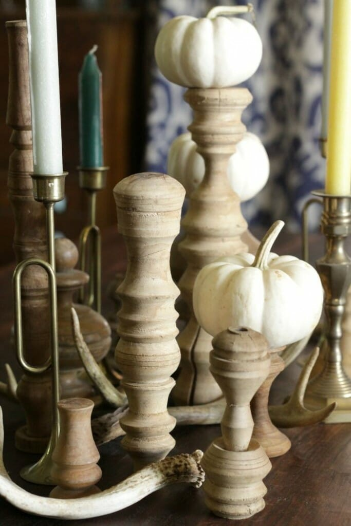Centerpiece wit brass candlesticks, blue and green candles, antlers, and stripped wood pieces