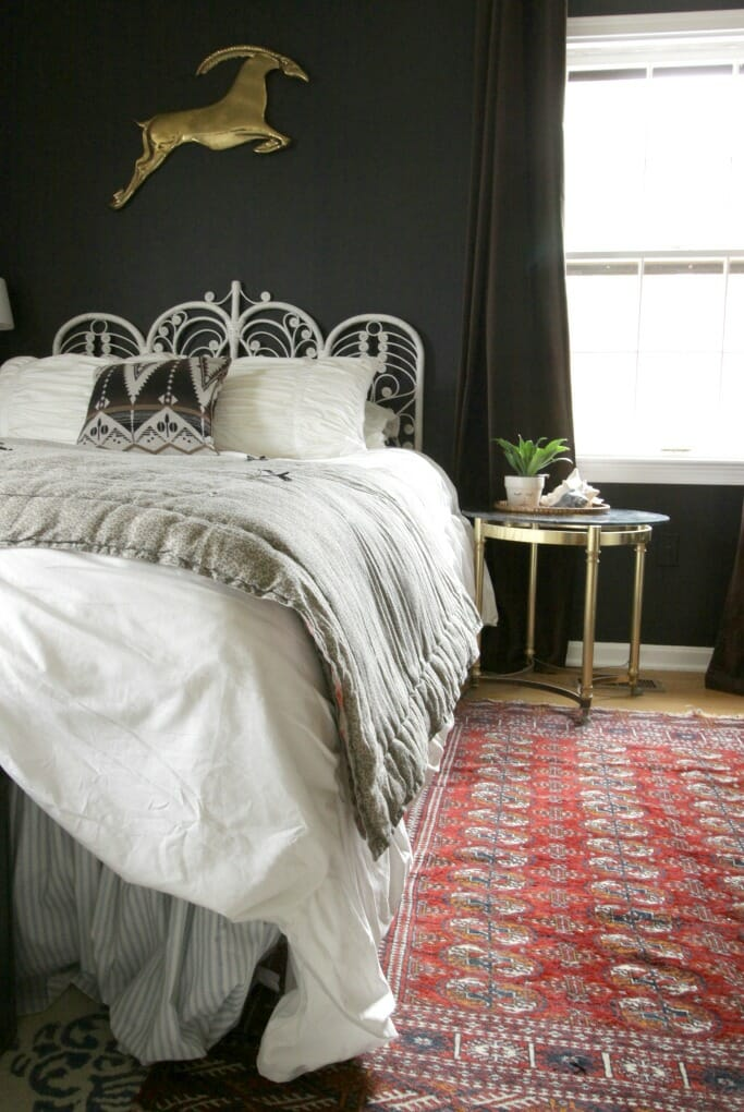 Eclectic Boho black bedroom with brass hoofed side tablt