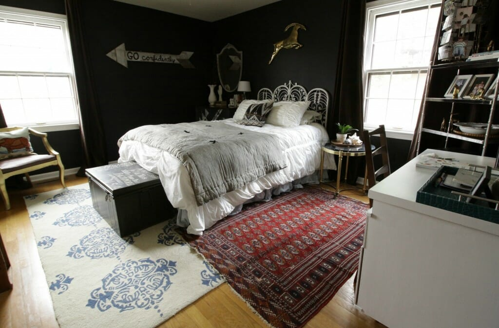 Office in a guest room- ecelectic bohemian bedroom with black walls