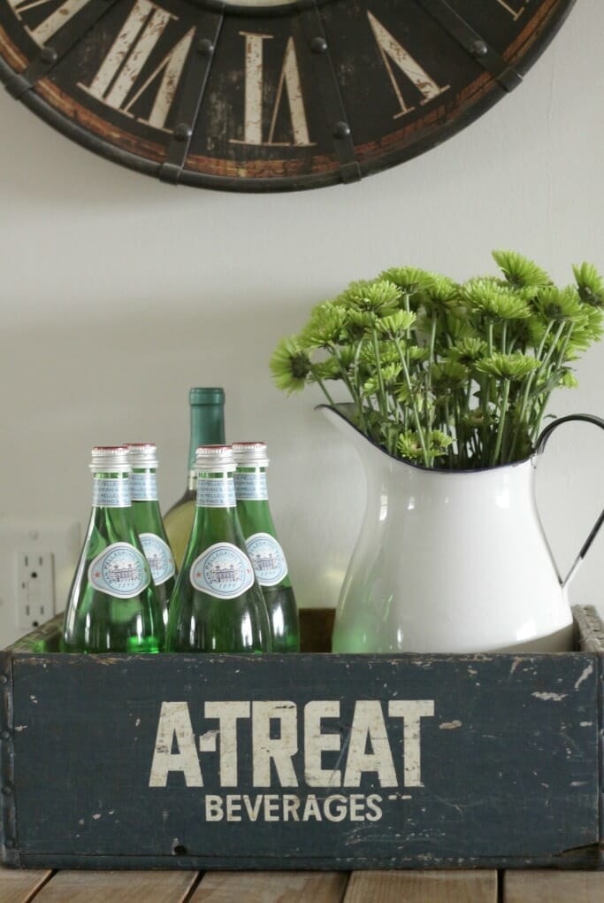 Vintage crate with green glass bottles and enamel pitcher and flowers