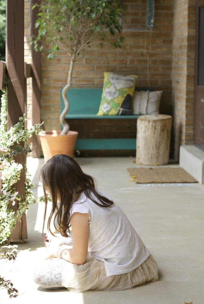Emmy drawing chalk on the porch.