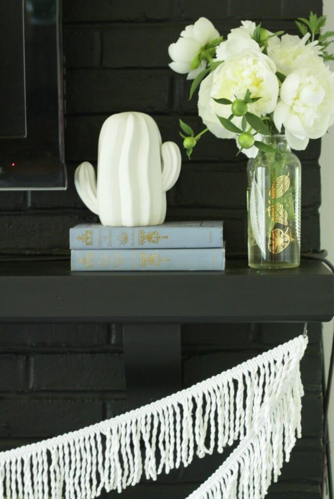 Cactus, Fringe, Peonies in white on black fireplace mantle